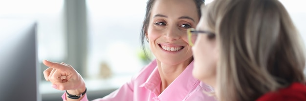 Deux femmes souriantes au bureau pointent vers les cours de programmation du moniteur à partir du concept de zéro