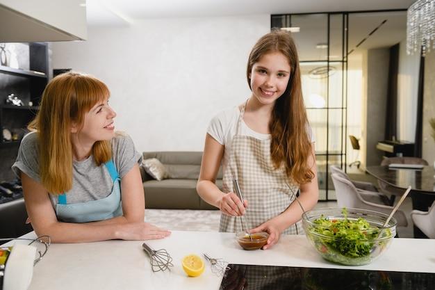 Deux femmes souriantes coupent une salade verte avec des tomates et mélangent la vinaigrette dans un petit bol avec du jus de citron, de la sauce noire et de l'huile à la cuisine
