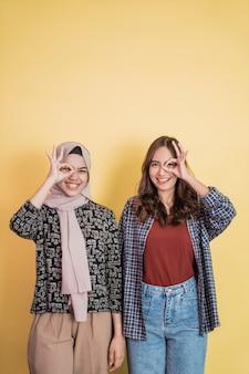 Deux femmes souriantes avec un geste de la main d'approbation ok apposée sur un œil avec fond au-dessus