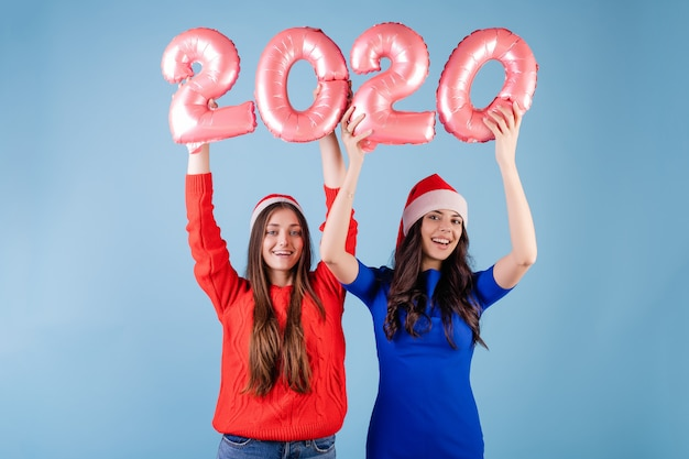 Deux, femmes souriantes, porter, chapeaux santa, tenue, 2020, ballons, pour, nouvel an, vacances, sur, bleu