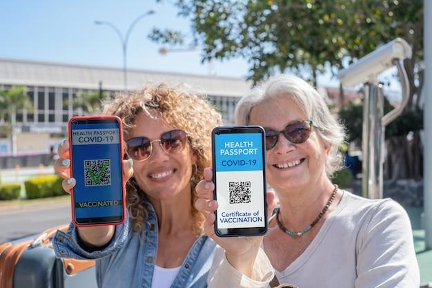 Deux femmes souriantes prêtes à voyager montrant une certification de santé numérique pour les personnes vaccinées contre le coronavirus. mère et fille heureuses insouciantes