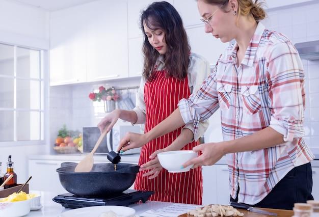 Deux femmes souriantes séduisantes cuisinent dans la cuisine moderne, deux amis s'amusent, des sœurs cuisinent ensemble.