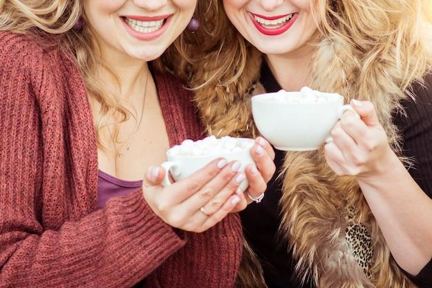 Deux femmes souriantes sont assises dehors avec des tasses de guimauves au chocolat chaud