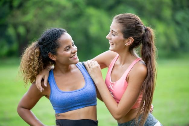 Deux femmes souriantes en tenue de sport profiter ensemble dans le parc