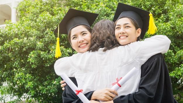 Deux femmes sourient et se sentent heureux dans les robes de graduation et casquette et se tiennent avec les parents