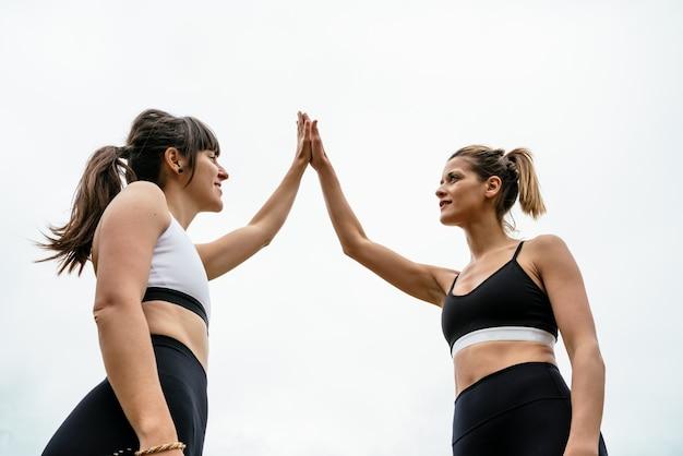 Deux femmes sportives high-fiving après une séance de sport sur un fond blanc