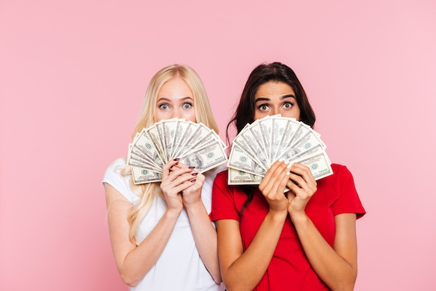 Deux femmes surpris se cachant derrière l'argent et regardant la caméra sur le rose