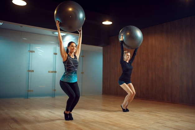 Deux femmes en tenue de sport, entraînement de pilates avec des balles dans une salle de sport. workuot de remise en forme dans un club de sport. personne de sexe féminin athlétique, aérobic intérieur, étirement du corps