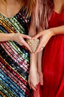 Deux femmes tiennent un cookie en forme de coeur lors d'une fête de la saint-valentin