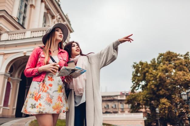 Deux femmes touristes cherchant le bon chemin en utilisant une carte à odessa. heureux amis voyageurs indiquant la direction