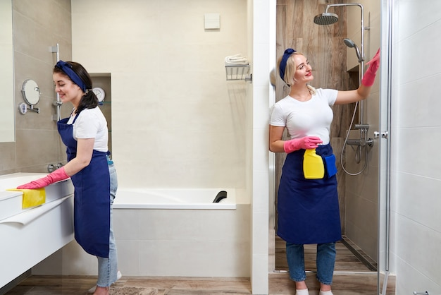 Deux femmes en uniforme debout dans une salle de bain moderne. concept de service de nettoyage