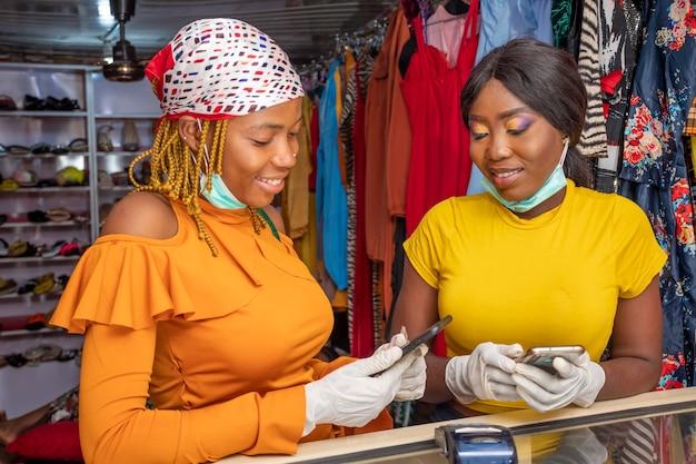 Deux femmes utilisant leur téléphone portable dans une boutique locale