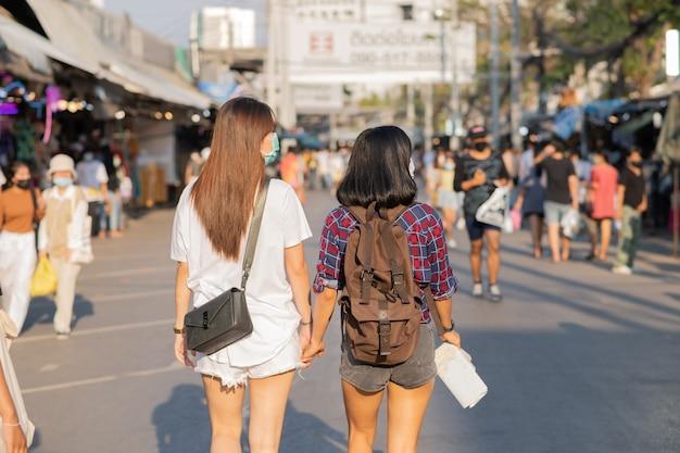 Deux femmes voyageant ensemble dans une rue animée.