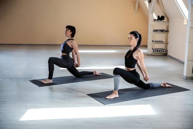 Deux femmes yogi flexibles en forme de lézard sur la pose de yoga du genou. intérieur du studio de yoga.