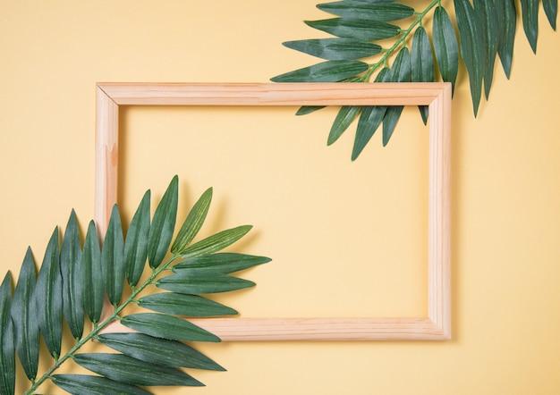 Deux feuilles de palmier et cadre en bois sur fond jaune. vue de dessus