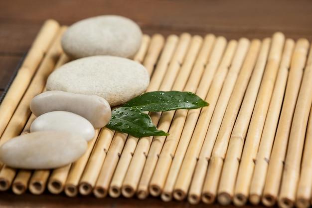 Deux feuilles vertes et quatre pierres blanches sur la natte de bambou