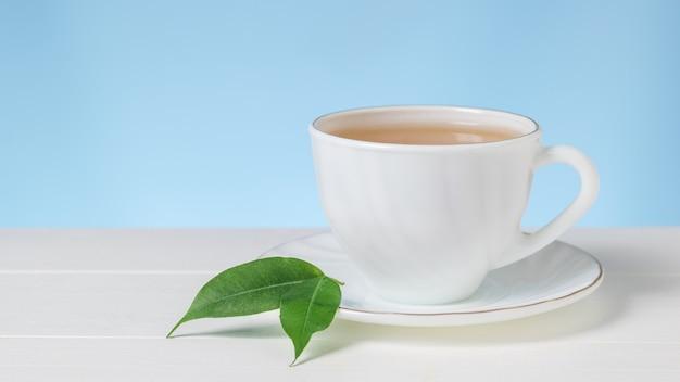Deux feuilles vertes sur une tasse de thé blanche sur une table blanche. une boisson vivifiante utile pour la santé.
