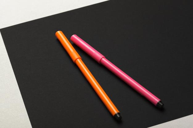 Deux feutres de couleurs rose et orange sur papier noir