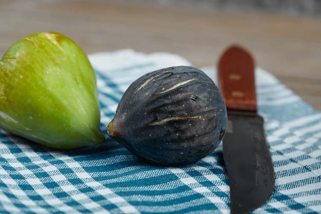 Deux figues et un couteau avec une nappe bleue sur une table en bois.