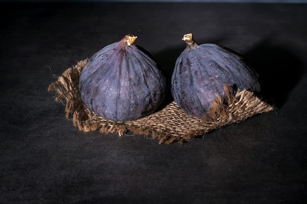 Deux figues violettes mûres reposent sur un tissu grossier et sur un dessus en béton.