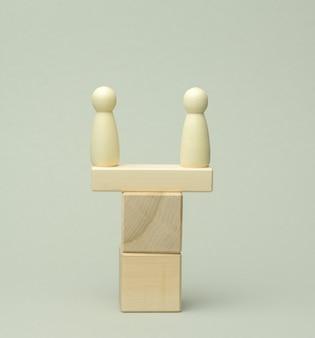 Deux figures en bois d'un homme sur une balançoire en barres