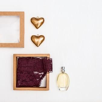 Deux figures de coeur, parfum, sous-vêtements féminins, boîte en papier cadeau. concept de fond de saint valentin. vue de dessus. mise à plat.