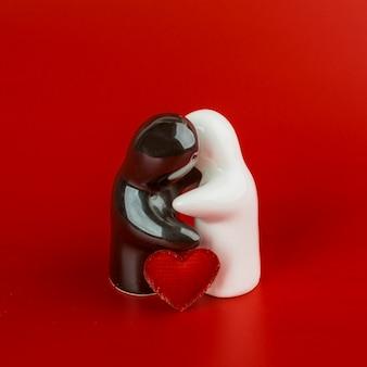 Deux figurines étreignant sur une table rouge
