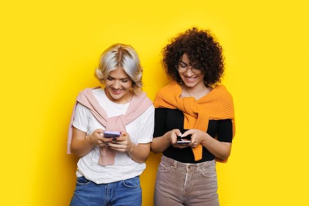 Deux fille aux cheveux bouclés discutant sur leurs téléphones sur un mur jaune