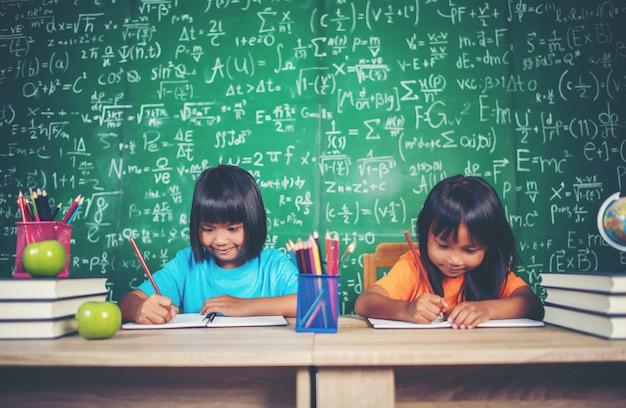 Deux fille avec un crayon dessin au cours dans la salle de classe