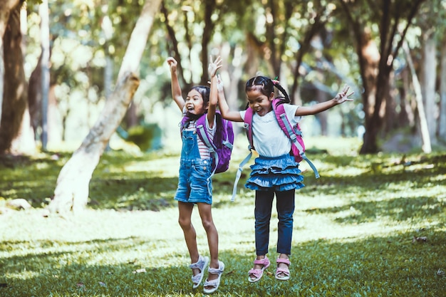 Deux fille mignonne enfant asiatique s'amusant à jouer et à sauter ensemble dans le parc