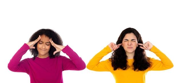Deux filles adolescentes ennuyées couvrant ses oreilles isolé sur un blanc