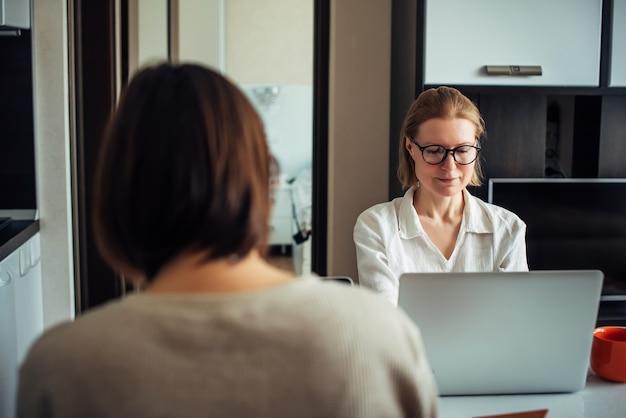 Deux filles adultes travaillant sur des ordinateurs portables à l'intérieur de la maison. freelance, coworking, travail, travail indépendant.