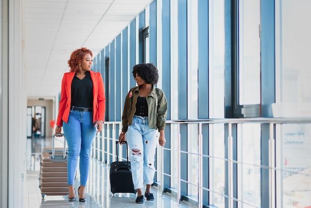 Deux filles africaines avec des valises à l'aéroport le concept de voyage et de vacances