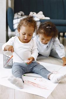 Deux filles afro-américaines dessinant sur un sol tout-petit et sa sœur aînée se noyant sur un papier