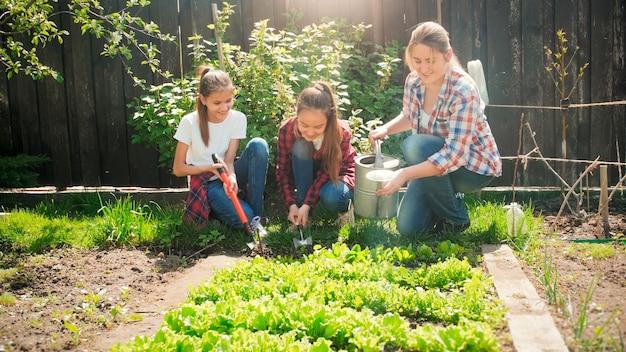 Deux filles aident leur mère à travailler dans le jardin et à arroser les légumes.