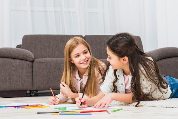 Deux filles allongées sur un tapis en train de dessiner avec des crayons de couleur dans le salon