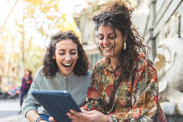 Deux filles amies utilisant un téléphone portable à l'extérieur