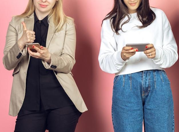 Deux filles, amis utilisant des smartphones mobiles. addiction des adolescents aux nouvelles tendances technologiques. fermer.