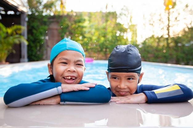 Deux filles asiatiques dans la piscine et jouer à l'eau avec plaisir