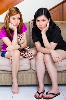 Deux filles asiatiques à la maison s'ennuient ou sont tristes