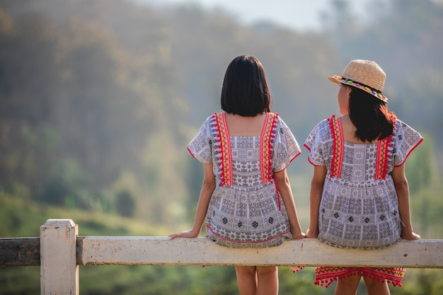 Deux filles asiatiques mignonnes et jeunes assis sur la barrière de jardin au coucher du soleil