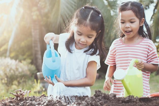 Deux filles asiatiques s'amuser à préparer le sol pour planter des jeunes arbres