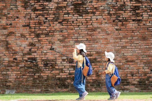 Deux filles asiatiques sont des blogueuses. diffusion sur internet. enregistrez les abonnés au vlog et au blog. enregistrez des leçons vidéo pour internet. utilisez un appareil photo avec un trépied.