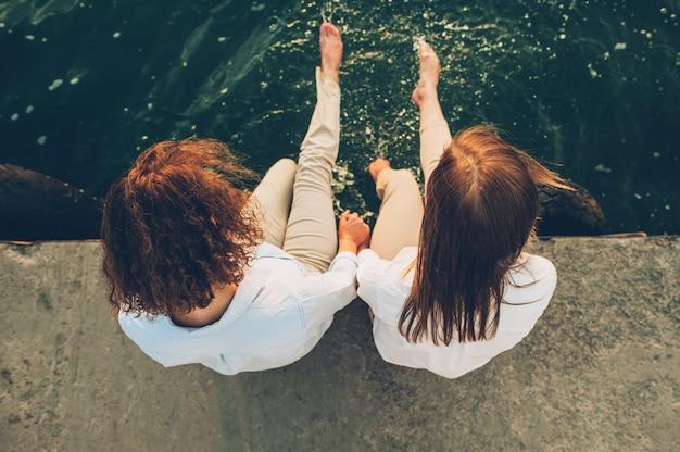 Deux filles assises sur la jetée