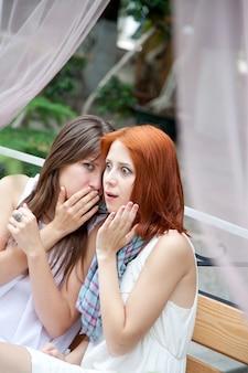 Deux filles bavardant sur un banc au jardin.