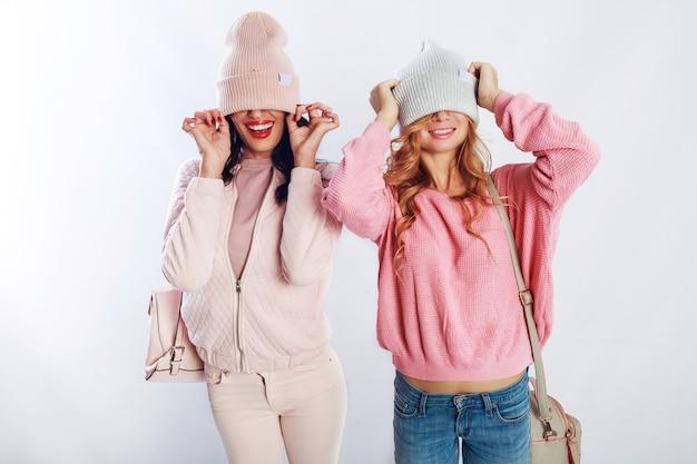 Deux filles bienheureuses en tenue tendance rose posant en studio sur fond blanc. amis mignons s'amusant, marchant, sautant,