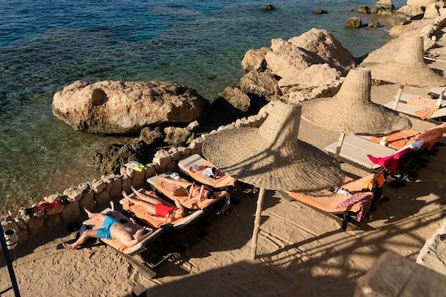Deux filles en bikini et un homme se font bronzer le matin sur des chaises longues sur fond de mer rouge.
