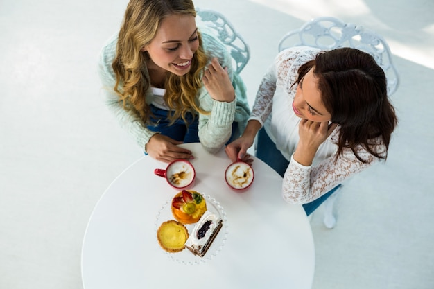 Deux filles boivent du café et mangent des pâtisseries