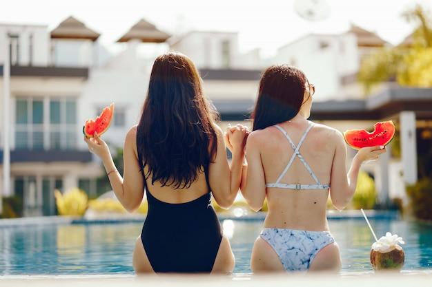 Deux filles bronzer et avoir des fruits au bord de la piscine