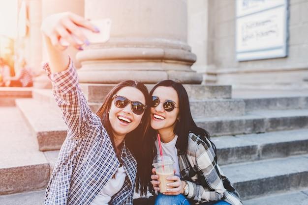 Deux filles brune aux cheveux longs faisant selfie en plein air